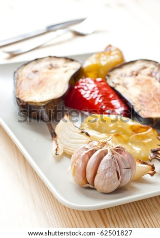 Baked onion, eggplant, colorful pepper and garlic on the plate