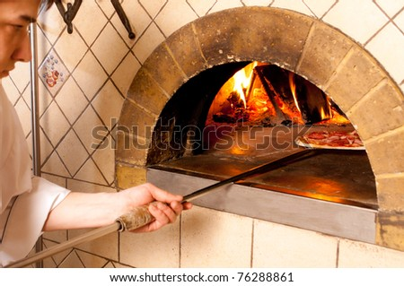 Baked pizza by the fire in traditional oven