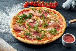 Baked pizza with salami, prosciutto and chicken with red sauce and melted cheese on a black wooden background in a composition with ingredients. Top view