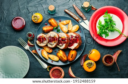Baked pork roll with autumn persimmon.Meat stuffed with fruits.Autumn food