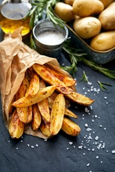 Baked potato fries with addition  sea salt and rosemary on a black background, top view