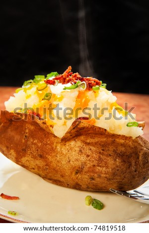 Baked potato loaded with cheese, green onion, sour cream, and bacon