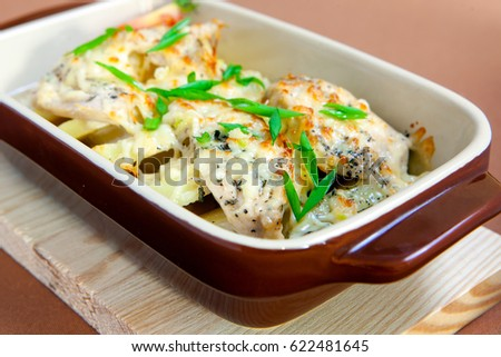 Baked potato slices under cheese decorated with green and tomato #622481645