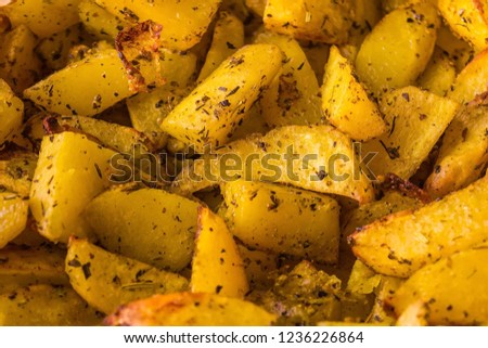 Baked potato wedges close-up. Vegetable side dish, simple food. Yellow potatoes sprinkled with spices. The edges are blurred. #1236226864