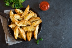 Baked potato wedges with cheese and herbs and tomato sauce on black background - homemade organic vegetable vegan vegetarian potato wedges snack food meal.