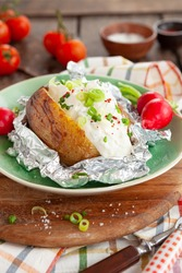 Baked potato with sour cream and fresh herbs