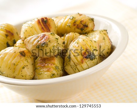 Baked potatoes with dill in bowl, selective focus