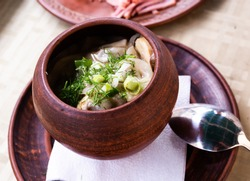 baked potatoes with mushrooms and herbs served in a ceramic pot