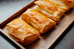 Baked puff pastry with toppings. Puffs with cheese on a wooden tray.