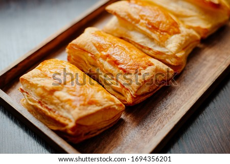 Baked puff pastry with toppings. Puffs with cheese on a wooden tray. ストックフォト ©