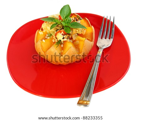 Baked pumpkin with rice, on a red dish it is isolated a bow, garlic and pips