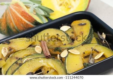 Baked pumpkin with sage and cinnamon in baking form