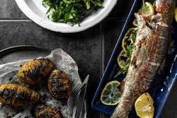 Baked rainbow trout and fresh vegetables with herbs and lemon straight out of the oven.