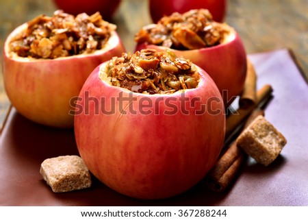 Baked red apples with granola and honey, close up view