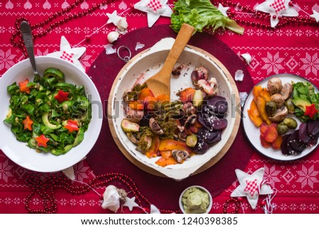 Baked, roasted, grilled vegetables in skillet pan with spatula. Beetroot, carrot, mushrooms, pumpkin, brussels sprouts with avocado dpi sauce. Xmas lunch, vegetarian Christmas dinner, healthy food