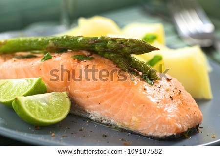 Baked salmon fillet with green asparagus, lime wedges and boiled potatoes (Selective Focus, Focus on the tip of the asparagus heads) - stock photo