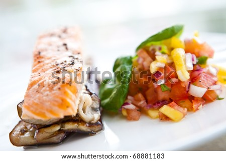 Baked salmon on bed of grill aubergine with serving of mango and tomato salsa