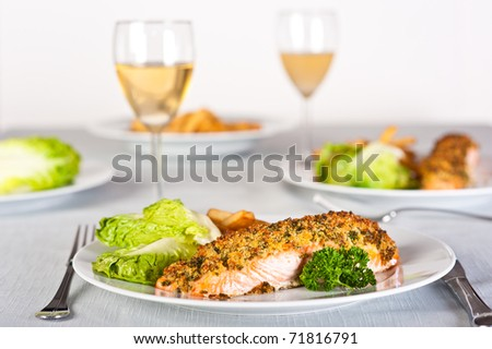 Baked salmon served with chips and salad greens.