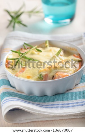 Baked salmon with asparagus and rosemary under cheese sauce in a baking dish