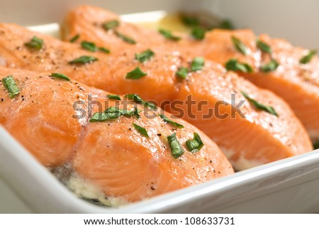 Baked salmon with shallots in casserole (Selective Focus, Focus on the front edge of the first salmon piece)