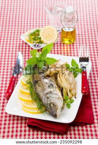 Baked sea bass with fennel lemon dill on white dish cloths to cell