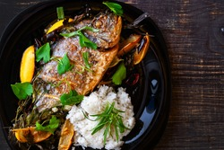 Baked sea gilthead with tarragon, parsley and rosemary with juicy fresh lemon and rice garnish close-up
