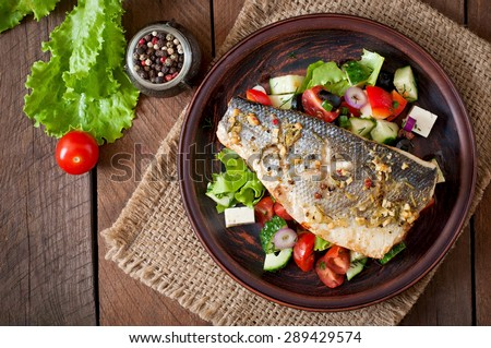 Baked seabass with Greek salad. Top view #289429574