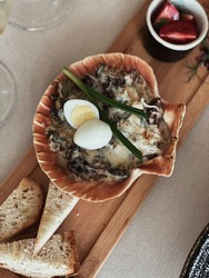baked shells in a shell restaurant serving decorated with a quail egg.serving the baked dish in the sink.restaurant serving seafood.
