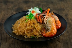 Baked Shrimp with Glass Noodles Vermicelli in Black Plate Chinese Food Asian Style decorate Corainder Thai Vegetable and carved Leek bunching onion sideview