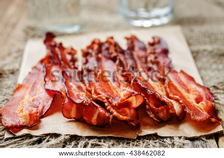 baked slices of bacon on a dark wooden background. toning. selective focus