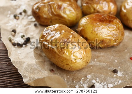 Baked spicy potatoes on parchment, closeup