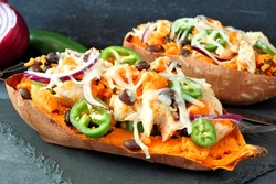 Baked sweet potatoes stuffed with chicken, vegetables and cheese, close up on dark background
