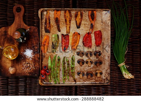 baked to a crisp vegetables spread out on a baking sheet in order, the two sides are two bundles of  onions