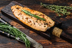 Baked trout fillet on a cutting board. Dark wooden background. Top view