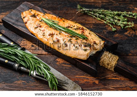 Baked trout fillet on a cutting board. Dark wooden background. Top view Stock photo ©