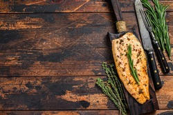 Baked trout fillet on a cutting board. Dark wooden background. Top view. Copy space
