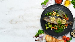 Baked trout fish with vegetables and lemon on a black plate. Top view. Free copy space.
