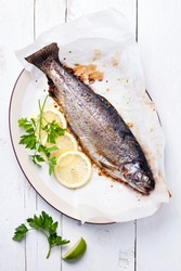 Baked trout with lemon and herbs on wooden background
