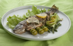 Baked trout with lemon, olives, lettuce and kidney bean on the white plate
