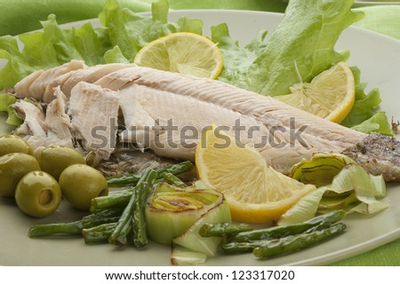 Baked trout with olives, lemon, leek and kidney bean on the plate