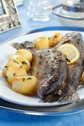 Baked trout with potatoes and lemon on plate
