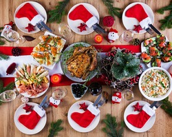 Baked turkey. Christmas dinner. The Christmas table is served with a turkey, decorated with bright tinsel and candles. Fried chicken, table.  Family dinner. Top view, flat lay, overhead, copy space
