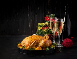 Baked turkey or chicken. The Christmas table is served with a turkey, decorated with bright tinsel. Fried chicken, table. Christmas dinner.