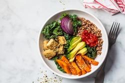 Baked vegetables, avocado, tofu and buckwheat buddha bowl. Vegan lunch salad with kale, baked sweet potato, tofu, buckwheat and avocado in a white bowl. Vegan concept.