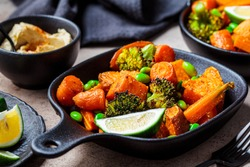 Baked vegetables in cast iron pans, dark background. Baked sweet potatoes, broccoli, carrots, and beans.