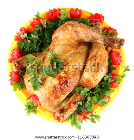 baked whole chicken with vegetables on a green plate isolated on white