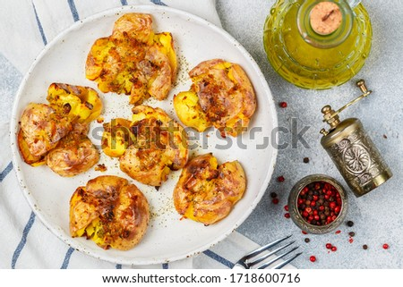 Photo of  Baked whole crushed and crusty potato with crust sea salt, olive oil, garlic, pink pepper and thyme in a white plate on a grey concrete background. Roasted smashed potatoes. Australian cuisine dish