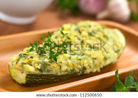 Baked zucchini stuffed with mashed potato, cheese and herbs (thyme, oregano, parsley, garlic) garnished with thyme on wooden plate (Selective Focus, Focus on the front of the thyme on the zucchini)