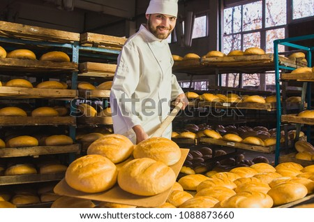 Baker. A young handsome bakery worker on the background of bread, takes bread from a stove with a wooden shovel. Industrial production of bakery products. a man in the baker's special clothing. Bakery Foto d'archivio ©
