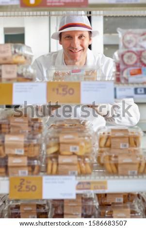 Baker Arranging Cake Display In Supermarket Bakery